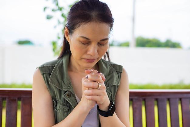 Mulher asiática orando manhã ao ar livre, mãos postas no conceito de oração pela fé, espiritualidade e religião, conceito online de serviços da igreja.