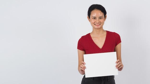 Mulher asiática ou jovem mão está segurando o papel em branco ou espaço de cópia a4 em fundo preto.