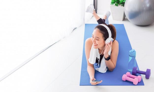 Mulher asiática, ouvindo música com fone de ouvido e smartphone depois de jogar ioga e exercício em casa.