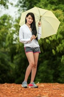 Mulher asiática, ouvindo música com um guarda-chuva