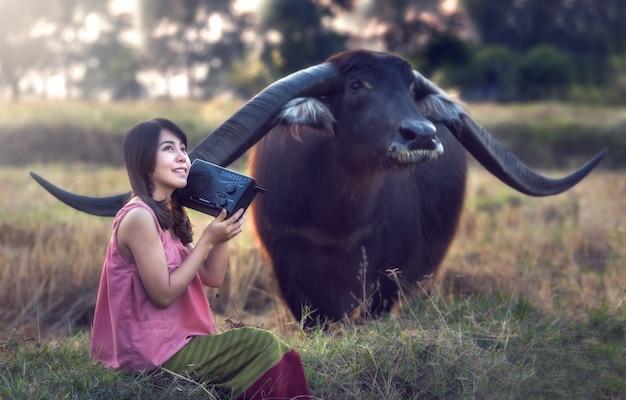 Mulher asiática ouvindo rádio com seu búfalo, tailândia