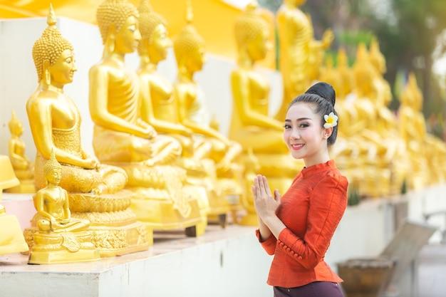 Mulher asiática para pagar o respeito à estátua da buda em tailândia.