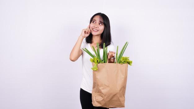 Mulher asiática pensando com um saco de papel de vegetais frescos com uma superfície branca isolada