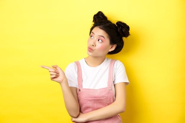 Mulher asiática pensativa com maquiagem de beleza, apontando e olhando para a esquerda com cara de curiosa, interessada em propaganda, parada no amarelo.