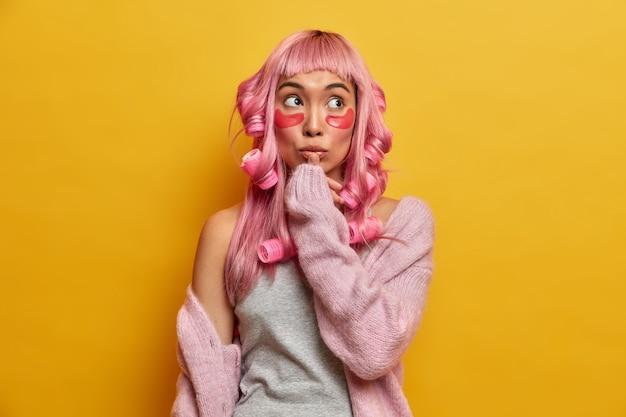 Mulher asiática pensativa de cabelo rosa, se prepara para uma ocasião especial, aplica compressas de colágeno e rolos de cabelo, toca os lábios, concentrado acima