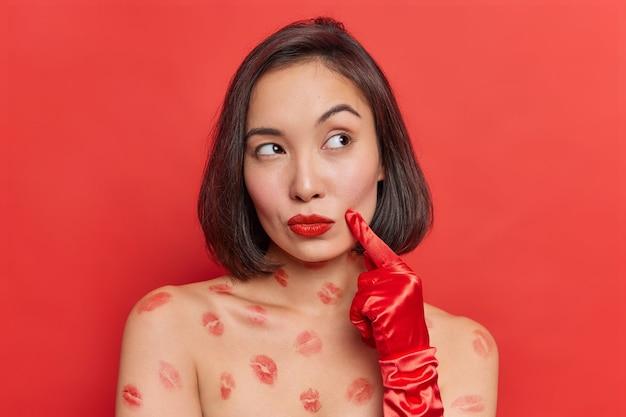 Mulher asiática pensativa e sonhadora mantém dedo na bochecha pensa sobre o amor tem traços de beijo no corpo pele lisa parece distante isolada sobre parede vermelha