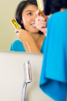 Mulher asiática, pentear o cabelo no espelho do banheiro