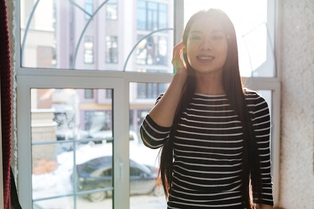 Mulher asiática perto da janela na cantina