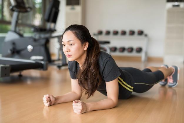 Mulher asiática planking no ginásio de fitness