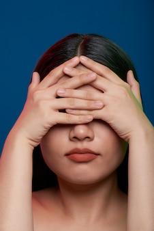 Mulher asiática posando no estúdio e cobrindo os olhos com os dedos entrelaçados