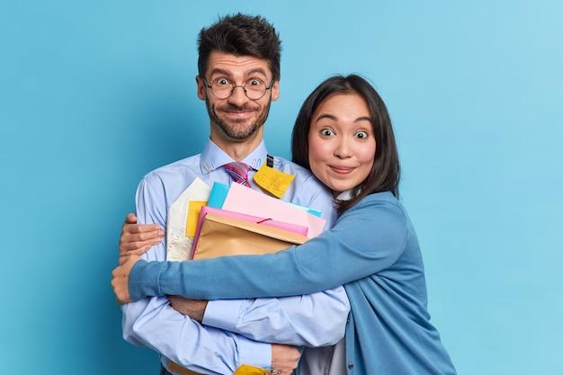 Mulher asiática positiva abraça seu colega e apóia ter relações amigáveis, olhar alegremente para a câmera. dois alunos engraçados e diversos posam