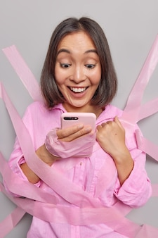 Mulher asiática positiva com expressão de alegria verifica a notificação no smartphone verifica os eventos que acontecem nas proximidades, verifica as notícias incríveis coladas na parede com fitas parecem tipos de caixa de correio na tela do celular