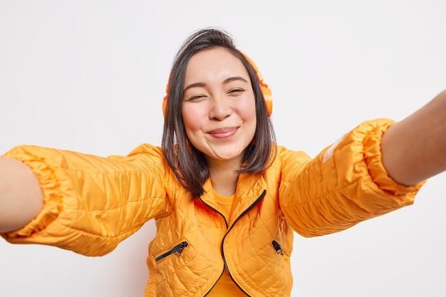 Mulher asiática positiva sincera estende o braço para frente faz selfie de bom humor ouve faixa de áudio usa fones de ouvido estéreo sem fio vestido com jaqueta isolada sobre parede branca