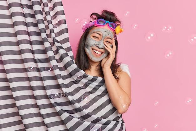 Mulher asiática positiva tem pele lisa e perfeita aplica máscara de argila sorri amplamente aplica rolos de cabelo para fazer poses de penteado encaracolado atrás da cortina gosta de poses de procedimentos higiênicos em torno de bolhas
