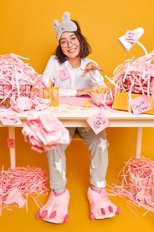 Mulher asiática positiva trabalha em casa durante a quarentena ou bloqueio, vestida com pijamas e prepara o trabalho do curso cercada por poses de papel cortadas em uma sala bagunçada contra a parede amarela