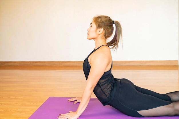 Mulher asiática pratica exercícios de treino de ioga no tapete de ioga em sua sala de estar em casa. estilo de vida saudável, novo conceito de quarentena normal ou doméstica