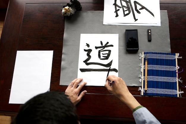 Mulher asiática praticando caligrafia japonesa dentro de casa