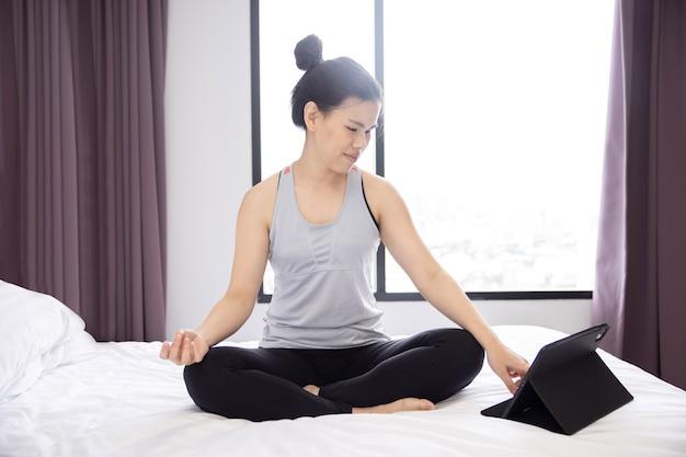 Mulher asiática praticando ioga aprendendo com seu tablet na cama pela manhã