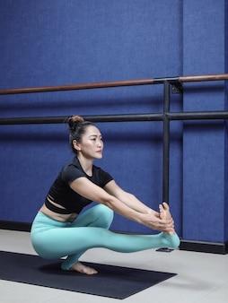 Mulher asiática praticando ioga avançada treinamento de alongamento físico