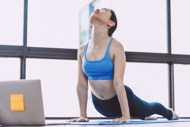 Mulher asiática praticando ioga em casa com um laptop quando a covid19 eclodiu e foi bloqueada