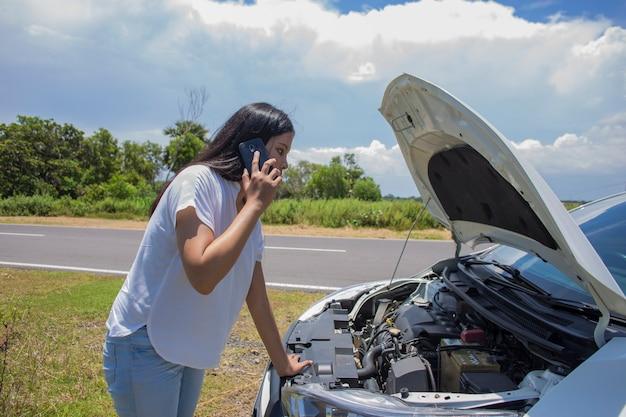 Mulher asiática precisa de ajuda com um carro quebrado com capô aberto