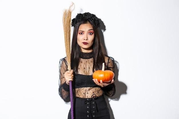 Mulher asiática preocupada e confusa na fantasia de bruxa, parecendo nervosa, segurando a vassoura e a abóbora, doce ou travessura no halloween, em pé sobre um fundo branco.