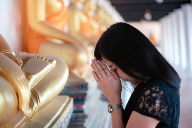 Mulher asiática presta homenagem à estátua de buda com respeito e fé