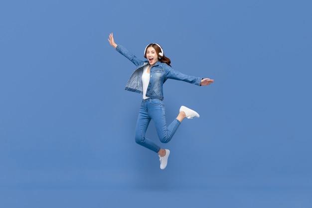 Mulher asiática pulando enquanto ouve música em fones de ouvido