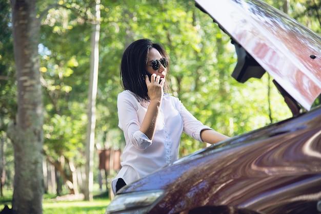 Mulher asiática que chama o reparador ou a equipe de seguros para corrigir um problema de motor de carro em uma estrada local