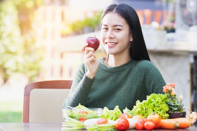 Mulher asiática que come o alimento saudável com feliz