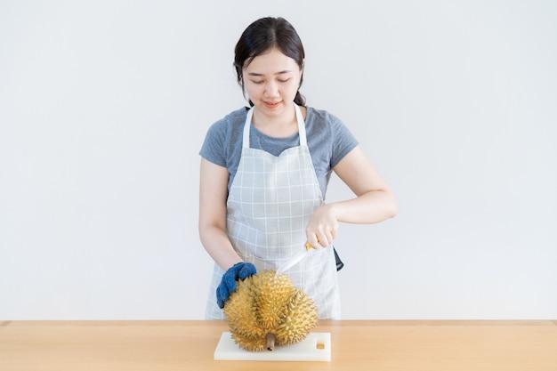 Mulher asiática que corta uma fruta do durian no fim de madeira da tabela acima. fruta durian, a fruta famosa e popular na tailândia.