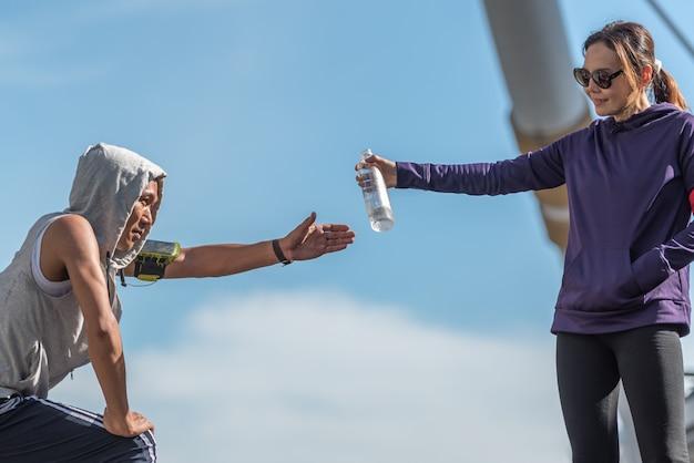 Mulher asiática que dá uma garrafa da água potável para ostentar o homem da aptidão.