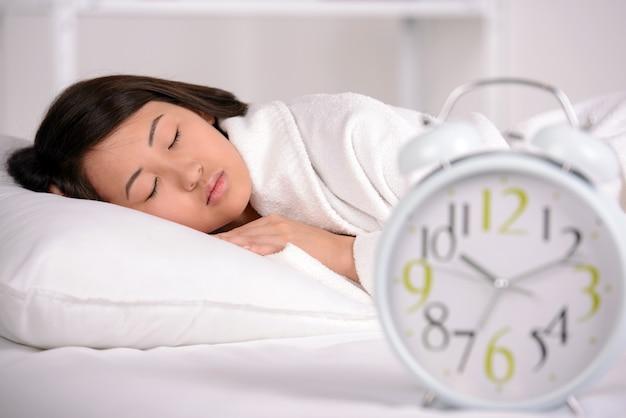 Mulher asiática que dorme na cama em casa.
