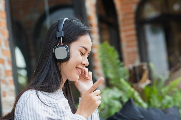 Mulher asiática que escuta a música com relaxe e feliz no tempo livre.