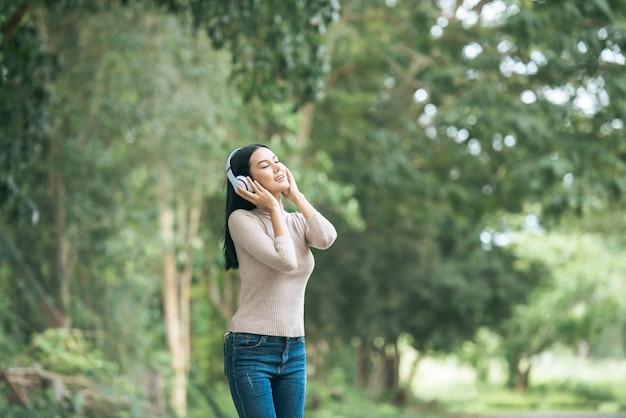 Mulher asiática que escuta música favorita em fones de ouvido. feliz tempo e relaxe.