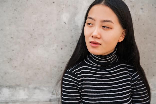 Mulher asiática que está contra a parede cinzenta.