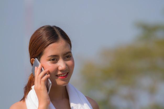 Mulher asiática que fala no telefone celular.