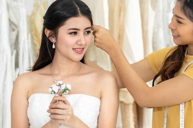 Mulher asiática que guarda a flor que mede no vestido de casamento em uma loja pelo alfaiate.