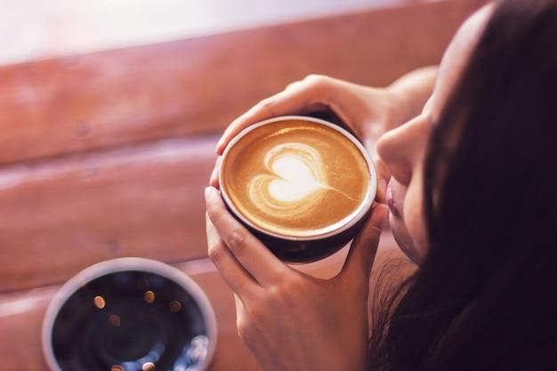 Mulher asiática que guarda as mãos na xícara de café. atividade de relaxamento. bebida favorita.
