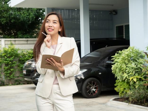 Mulher asiática que guarda o caderno ao estar na frente da casa.