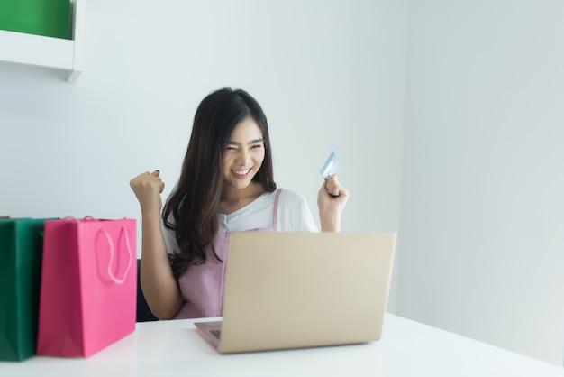 Mulher asiática que guarda o cartão de crédito e que usa o laptop.