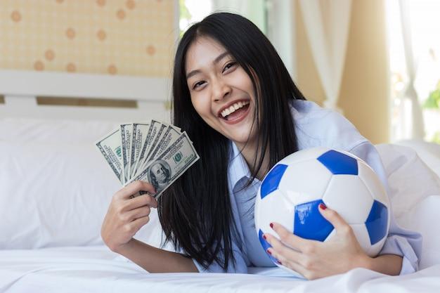 Mulher asiática que guarda o dinheiro e o futebol no quarto. sorte jogando