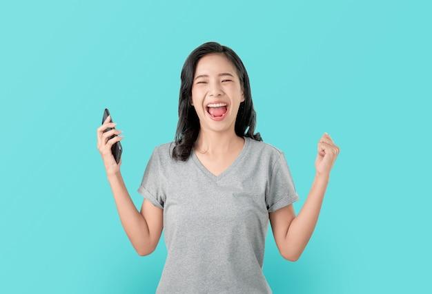 Mulher asiática que guarda o smartphone com espantado para o sucesso e que olha para a frente no azul.