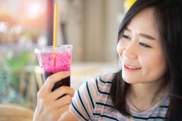 Mulher asiática que guarda um suco das beterrabas com feliz, conceito em comer saudável.