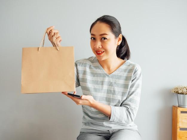 Mulher asiática que mostra fora o saco de papel vazio do produto que comprou em linha. conceito de compras on-line.