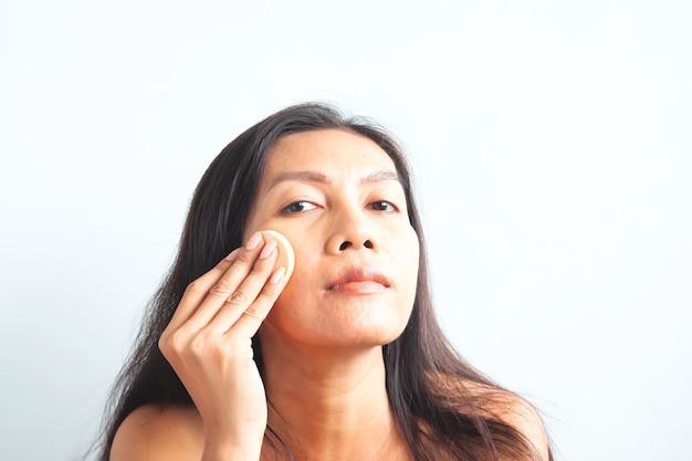 Mulher asiática que olha a câmera e que aplica o pó da fundação em sua cara. conceito de beleza