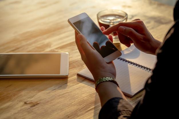 Mulher asiática que olha fixamente em seus telefones celulares ao trabalhar.