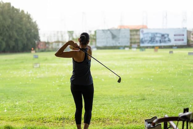 Mulher asiática que pratica seu balanço do golfe na escala de condução do golfe.