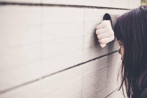 Mulher asiática que senta-se sozinho e deprimido, retrato da jovem mulher cansado. depressão