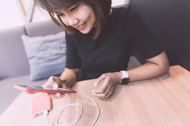 Mulher asiática que sente feliz com smartphone ao cobrar com o banco do poder.